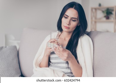 Portrait of troubled ill young woman sitting at home holding glass of water and reading discription of medication in her hand