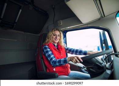 Portrait of trucker sitting in truck cabin with hands on steering wheel.