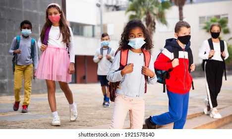 Portrait of tween girl in medical face mask on her way to college on warm autumn day. Forced precautions in COVID pandemic