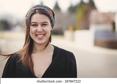 Portrait of a twenty-four year old woman on the street wearing a slouch hat she crocheted for herself. Casually dressed with no makeup.
