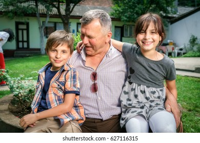 Portrait of a twin brother and sister with Grandfather. Little cute kids playing in the backyard.