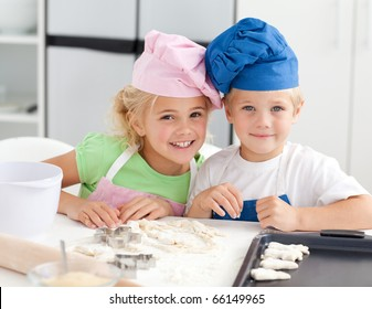 Portrait of two adorable children baking in the kitchen at home