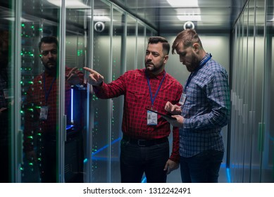 Portrait of two adult bearded man standing in corridor of server room in data center smiling at camera