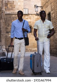 Portrait of two aframerican tourists in light clothes walking around summer city with suitcases