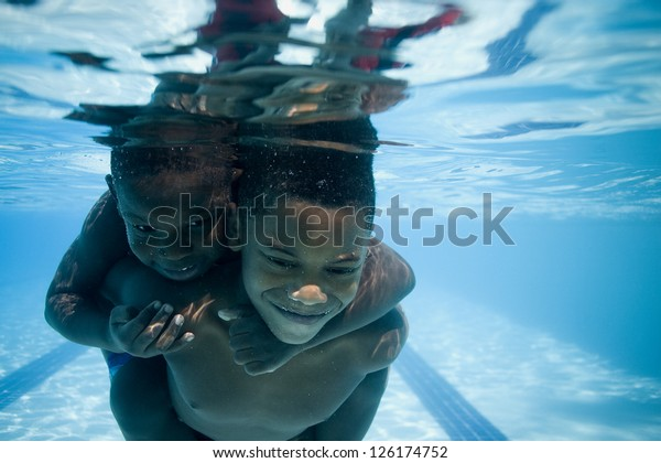 Portrait of two African American boys swimming underwater