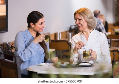 Portrait of two american women with tea and chocolates in cafe