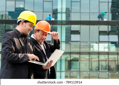 Portrait of two architect using laptop against building background