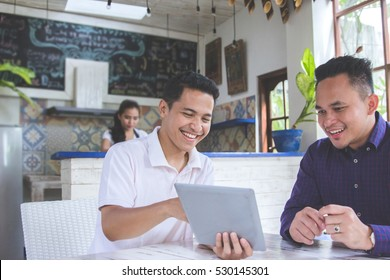 portrait of two asian Business people Working with tablet In cafe