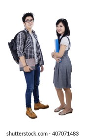 Portrait of two Asian college students standing in the studio and smiling at the camera, isolated on white background