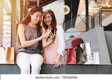 Portrait of two asian women sharing news and using smartphone with shopping bags, black friday and shopping online concept