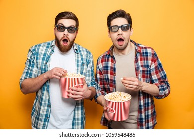 Portrait of a two astonished young men in 3d glasses eating popcorn while standing isolated over yellow background