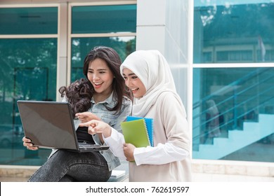 portrait of two attractive asian college student using laptop on campus