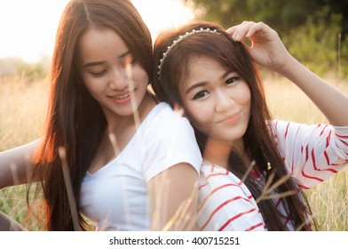 Portrait of two attractive asian smiling women in the garden