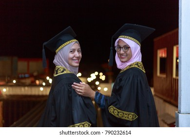 Portrait of two attractive joyful women wearing veil and graduation dress. Selective focus.