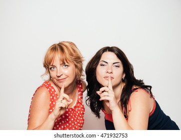 Portrait of two attractive women with finger on lips