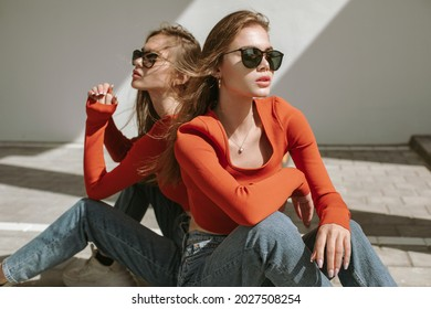 Portrait of two attractive young girls in sunglasses and identical clothes posing in urban area in diagonal shadow in sunlight.