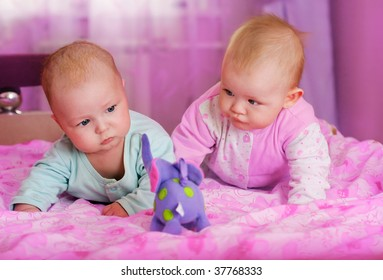 portrait of two babies in pink room