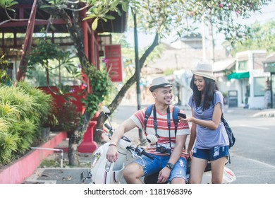 portrait of two backpackers with summer hat seeing the result of their photo on mobilephone