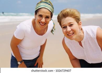 Portrait of two beautiful 45 years old women walking on seaside