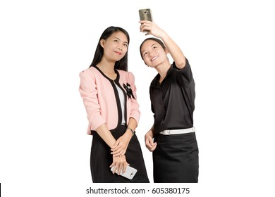portrait of two beautiful asian business woman smiling and making a selfie with smart phone. Isolated on white background with copy space and clipping path