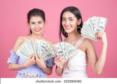Portrait of two beautiful asian smiling young women doing shopping. Woman holding dollar for shopping. isolated on pink background