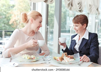 Portrait of two beautiful businesswomen sitting looking at each other smiling holding cups of coffee, salad in big plates in front of them, in a restaurant during business lunch, selective focus