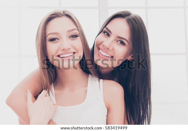 Portrait of two beautiful cheerful girls with beaming smiles huging