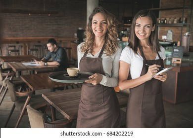 portrait of two beautiful female waitress smiling to camera