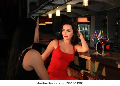 Portrait of two beautiful female who sit at the bar in a nightclub and drink cocktails.