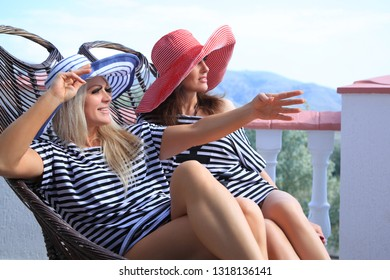 A portrait of two beautiful girlfriends sitting on a wicker chairs, watching from the balcony. Close-up. Without looking at the camera.