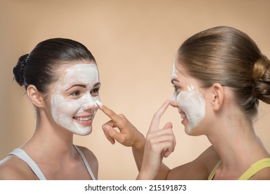 Portrait of two beautiful girls with cream on their  faces looking on each other  and touching their noses and laughing  isolated on beige background with copy placer