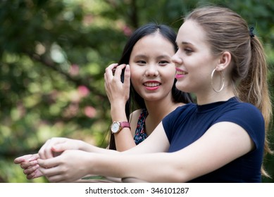 Portrait of two beautiful girls talking in the park
