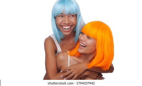 Portrait of two beautiful happy Asian women friends in bright blue and orange wig posing over white background
