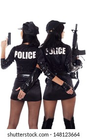 Portrait of two beautiful sexy policewomen with handcuffs in a black uniform that aiming a submachine gun. isolated on white.