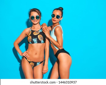 Portrait of two beautiful sexy smiling hipster women in summer swimwear bathing suits. Trendy hot models having fun in studio in sunglasses. Girls isolated on blue