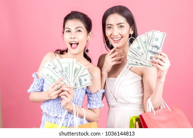 Portrait of two beautiful women holding shopping bags and enjoying shopping on pink background