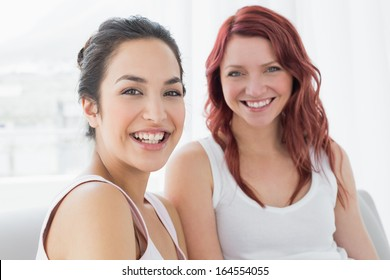 Portrait of two beautiful young female friends smiling in the living room at home