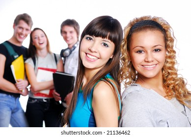 Portrait of two beautiful young female students on a foreground. On a blur background laughing classmates.