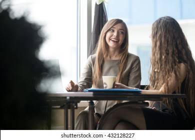 Portrait of two beautiful young girlfriends sitting in modern coffee shop interior and talking with happy smiles. Successful attractive women friends chatting in cafe during coffee break