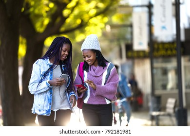 Portrait of two beautiful young woman using mobile phone in the street.