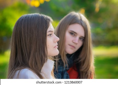 Portrait of two beautiful young women rivals sitting side by side on a bench.