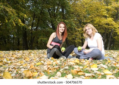 Portrait of two beautiful young women sitting together and eating green apple