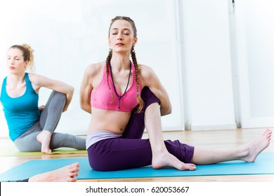 Portrait of two beautiful young women practicing yoga at home.