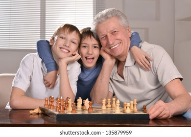 Portrait of two boys and grandfather playing chess at home