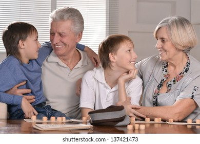 Portrait of two boys and grandparents playing lotto at home