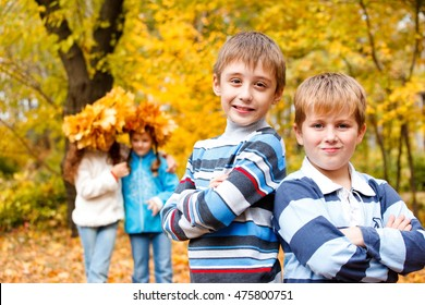 Portrait of two boys of a school age and two girls standing behind in an autumn park