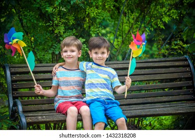 Portrait of two boys, sibling brothers and best friends smiling. Kids sitting on bench play together with pinwheel. Outdoors leisure friendship family concept.
