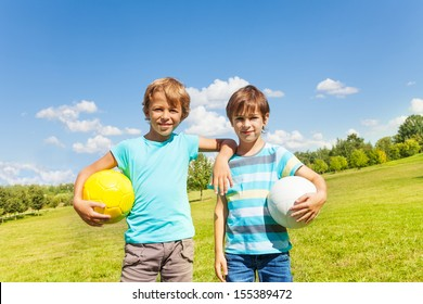 Portrait of two brothers boys stand with holding balls standing in the park on sunny summer day