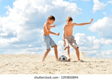 Portrait of two brothers playing football on beach in summer day
