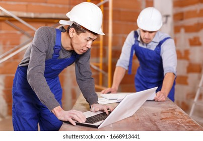 Portrait of two builders reading plan of brick building using laptop